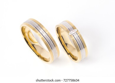 Golden striped wedding rings on pure white background, vertical orientation.