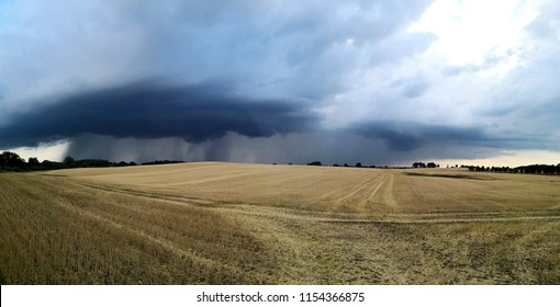 golden stubble wheat field under grey sky with torrential rain