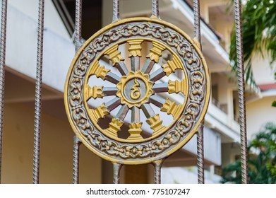 Golden stucco of the Wheel of the dharma and decorate by little blue glass, the dharma wheel, known as the dharmachakra, as a symbol in Buddhism