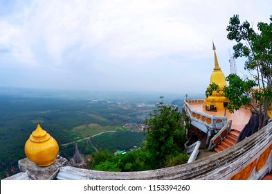 Golden stupa at the top of the Wat Tham Sua with the Krabi coastline in the background