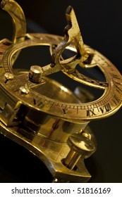 A golden sun dial combined with a compass.