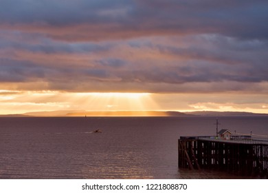 Golden sun rays shining through dramatic blue and magenta colored clouds over Penarth Pier and the sea.