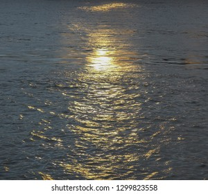 Golden sun reflection on the water surface.