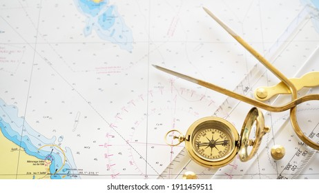 """Golden sundial, antique vintage W HC 6"""" brass dividers calipers nautical navigation chart tool, parallel ruler, old white chart close-up. Vintage still life. Sailing, travel accessories"""