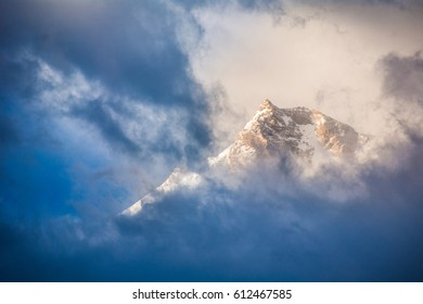 Golden sunrise behind dark blue clouds passing over the peak of Nanga Parbat mountain in the Himalayas in northern Pakistan