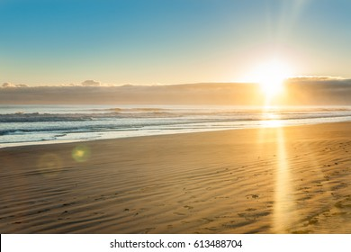 Golden sunrise and lens flare over wide flat sandy beach at Ohope Whakatane, New Zealand.