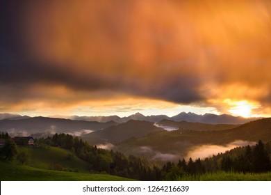 Golden sunrise in the mountains of Kamnik Savinja Alps and rolling fog in Skofjelosko Hills with St Thomas church near Ljubljana Slovenia
