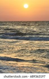 Golden sunrise on the sea coast. Vertical