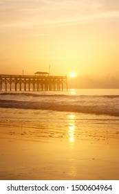 Golden sunrise over Atlantic ocean beach. Scenic marine landscape with wooden pier and calm ocean in soft sun light during sunrise at Pawleys Island, South Carolina, USA. Vertical composition.