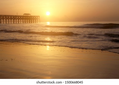 Golden sunrise over Atlantic ocean beach. Scenic marine landscape with wooden pier and calm ocean in soft sun light during sunrise at Pawleys Island, South Carolina, USA.
