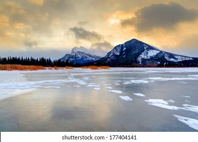 Golden sunrise over frozen Vermilion Lakes in Banff National Park with Mt. Rundle in the background.