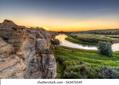 Golden sunrise over the Hoodoo badlands at Writing-on-Stone Park and Aisinaipi National Historic Site in Alberta, Canada. The area has large findings of First Nation petroglyphs and pictographs.