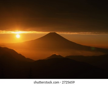 Golden sunrise over Mt. Fuji as viewed from an adjacent peak.