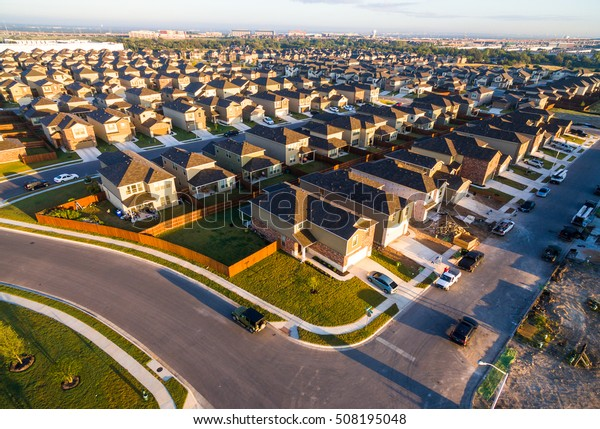 Golden Sunrise with row after row of Surburbia Houses Aerial Sunrise Over New Development Suburban Homes in North Austin Texas