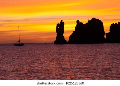 Golden sunrise with silhouette of sailboat and rock islands in Baja California Sur, Mexico with purple sea.
