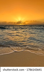golden sunrise or sunset over a caribbean beach with a wave rolling in