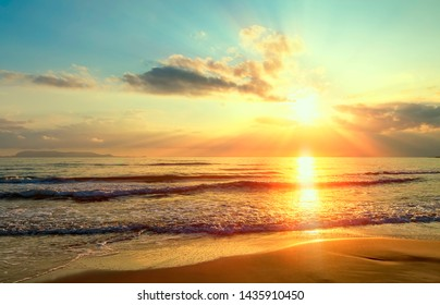 Golden sunrise sunset over the sea ocean waves. Rich in dark clouds, rays of light