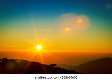 Golden sunrise or sunset sky with sun flare on the mountains with sun beams landscape. Dramatic sky background, Doi Inthanon, Chiangmai Thailand.