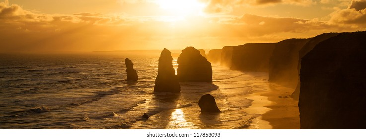 Golden sunset at 12 Apostles rock formation in Victoria, Australia. Dusk sun setting behind the backlit apostles with sea fog rolling in to the cliff face.