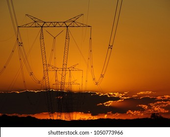 Golden sunset. Big antennas of high voltage are placed in a row. In the distance you can see big clouds and the shape of some shrubs.