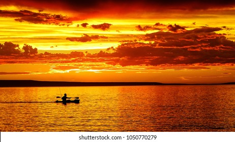 Golden sunset with big clouds in a lake located in Patagonia, Argentina. The shape of man rowing in a canoe with a small rod by his side can be seen. Summer.