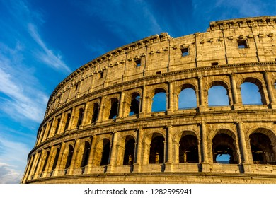 Golden sunset at the Great Roman Colosseum (Coliseum, Colosseo), also known as the Flavian Amphitheatre. Famous world landmark. Scenic urban landscape.