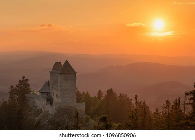 Golden sunset in Kasperk castle, Sumava, Czech Republic. Hills and villages in the fog, misty view on Czech landscape, evening scene.