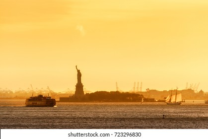Golden Sunset in Manhattan Bay with the Silhouette of the Statue of Liberty