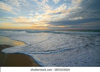 Golden sunset on the beach and low sea waves brake the shore. Tranquil scene, beautiful cloudy sky on background