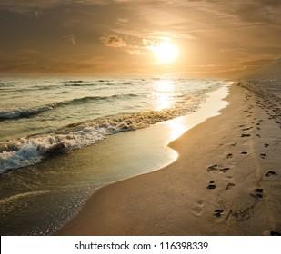 goldener Sonnenuntergang am Meer und Fußspuren im Sand