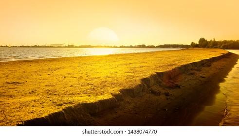 Golden sunset on the Volga River in Astrakhan. Sandy spit.