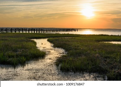 Golden Sunset Over Coastal Inlet and Pier