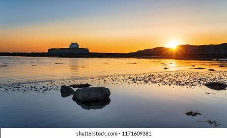 Golden sunset over Cwyfan church on Anglesey in north Wales