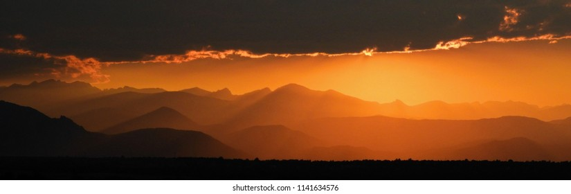 Golden sunset over the  front range of the colorado rocky mountains, as seen from broomfield, colorado