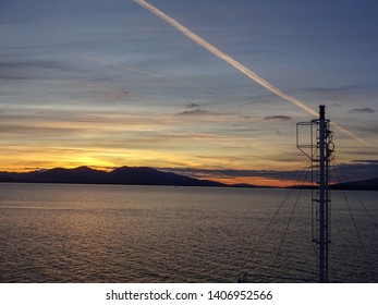 Golden sunset over Oban Bay looking to the Isle  of Mull in Scotland Great Britain with mast of ferry and contrails in the sky