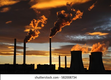 golden sunset over smoking power house plant factory