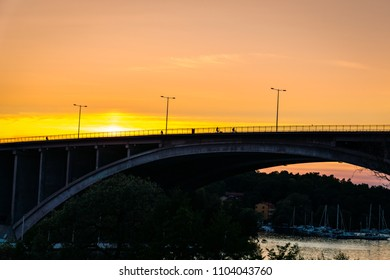 Golden sunset with people cycling on a bridge over water with boats underneath.