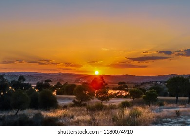 Golden sunset with rays in the haze and clouds in Ayamonte, Andalucia, Spain looking accross to Portugal over the Guadiana River seen from Costa Esuri
