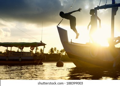 Golden sunset silhouettes of children diving from the bow of a boat in the northeast Nordeste coast of Brazil