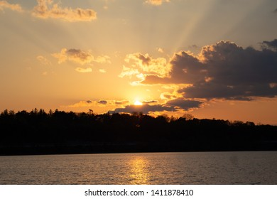 Golden sunset with sunrays breaking through clouds over a lake.  The background is a forest and hills.