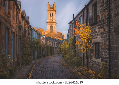 Golden sunset or sunrise light over the picturesque and quaint Circus Lane and St Stephen's Church clock tower with autumn colours in Edinburgh, Scotland