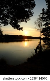 Golden sunset or sunrise with tree silhouettes over a forest lake with the sky reflected on the surface of the water