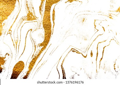 Golden swirl, artistic design. Suminagashi – the ancient art of Japanese marbling. Paper marbling is a method of aqueous surface design. White paper and gold texture.