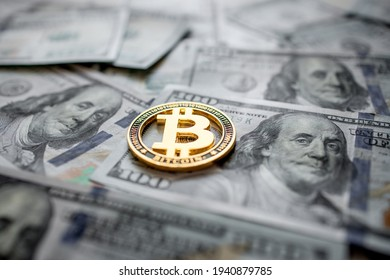 Golden symbolic coin Bitcoin on banknotes of one hundred dollars. Exchange bitcoin cash for a dollars. Cryptocurrency on US dollar bills. Digital modern method of payment. Savings, investments concept - Shutterstock ID 1940879785
