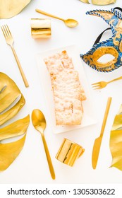 Golden table setup with tropical monstera leaf painted with golden in the corner.golden cutlery, a mask of carnival and the typical italian carnival sweets scrapple, a fried pastry.