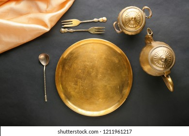 Golden tableware on black background