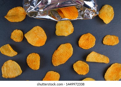 golden tasty potato chips with a bag, flat lay
