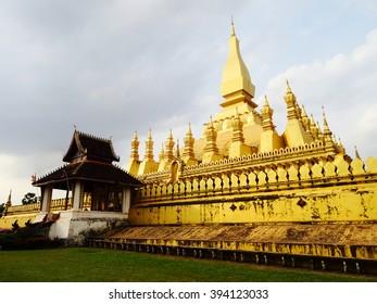 Golden temple in Laos under cloudy sky.