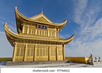 A golden temple at the top of the hill with blue sky