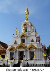 A golden Thai temple under a clear blue sky in rural Thailand.